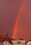 Rainbow over old town. Against a pink lavender sky Royalty Free Stock Image