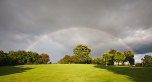 Rainbow over an orchard in summer Royalty Free Stock Image
