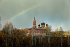 Rainbow over the Orthodox monastery and the autumn forest.  Royalty Free Stock Photography