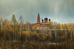 Rainbow over the Orthodox monastery and the autumn forest.  Stock Photo