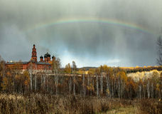 Rainbow over the Orthodox monastery and the autumn forest Stock Images