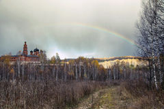 Rainbow over the Orthodox monastery and the autumn forest Stock Image