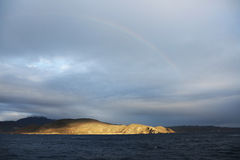 Rainbow Over Pacific Peninsula. A beautiful rainbow after the storm arcs over a peninsula reaching into the Pacific Ocean Royalty Free Stock Images