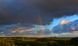 Rainbow over a paddock at sunset. A rainbow coming down from grey clouds into a paddock at sunset Stock Images