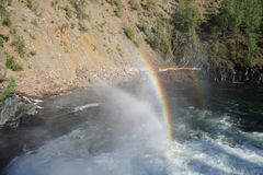 Rainbow over a powerful flow of water under the waterfall of the river Urich in the Eastern Sayan Stock Photography