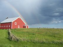 Rainbow over a red barn.. the best things in life are free. Sure, you have to milk the cows an clean the stalls in the barn on a dreary, rainy day... but then Stock Photography