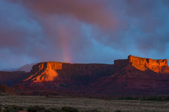 Rainbow over red rock Mesa in Utah during storm and sunset. Rainbow and storm sunset in Canyon country of Southern Utah Royalty Free Stock Photos