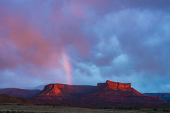 Rainbow over red rock Mesa in Utah during storm and sunset. Rainbow and storm sunset in Canyon country of Southern Utah Royalty Free Stock Photo