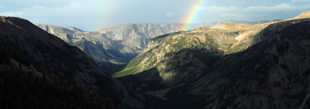 Rainbow over a remote mountain range. With steep valleys in a beautiful tranquil landscape, panoramic view Stock Photos