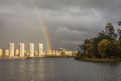 Rainbow over the residential area at the edge of the lake Royalty Free Stock Image