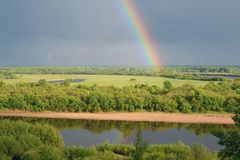 Rainbow over the river. Bright rainbow over the river after evening rain stock photos
