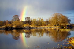 Rainbow over river. A rainbow forming near a river Royalty Free Stock Image