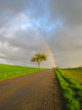 Rainbow over road. Beautiful rainbow over the road stock images