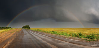 Rainbow over road. Landscape with road, storm clouds and rainbow Stock Image