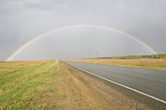 A rainbow over a road. Stock Photo