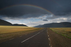Rainbow over the road. Lowering clouds and rainbow over the road Royalty Free Stock Photos