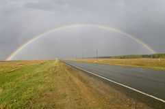 A rainbow over a road. Russia. royalty free stock photography
