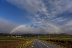 Rainbow over a road to the village Royalty Free Stock Photos