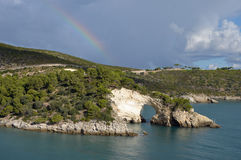 Rainbow over the rock window near Vieste Stock Photos