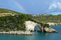 Rainbow over the rock window near Vieste Stock Image