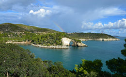 Rainbow over the rock window near Vieste Stock Photos