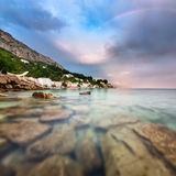 Rainbow over Rocky Beach and Small Village after the Rain Royalty Free Stock Photography