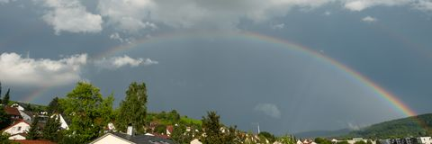 Rainbow over roofs at a dark sky Royalty Free Stock Photo