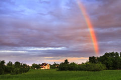 Rainbow over rural Village. Vibrant rainbow over rural village scene after a storm Royalty Free Stock Photos