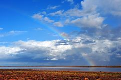 Rainbow over a Salt Lake, with Storm Clouds moving across the Sky. Thermals developing after rain water in the Salt lakes.nRainbow over a Salt Lake, with Storm royalty free stock image