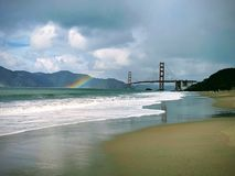 Rainbow next to the golden gate bridge off of the beach with rain clouds and mountains in the background stock photos