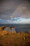 Rainbow over the sea. A rainbow over the sea and in the foreground the cliffs Stock Photos