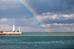 Rainbow over the sea. And a beacon Royalty Free Stock Image
