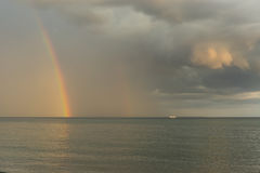 Rainbow over the sea. Against a gray sky Stock Image