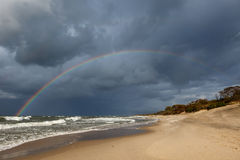 Rainbow over the sea and the beach. Royalty Free Stock Image