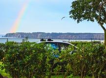 Rainbow over sea coast. Stock Photos
