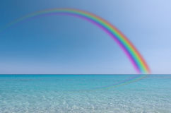 Rainbow over the sea. Rainbow reflection on the surface of the sea Royalty Free Stock Images