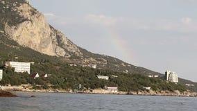 Rainbow over sea shore stock footage