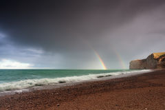 Rainbow over sea waves by rock after shower Stock Image