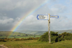 Rainbow over a signpost with destinations, UK. Royalty Free Stock Photography