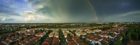 Rainbow over sky and home village Stock Images