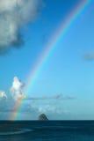 Rainbow over small island Stock Photos