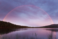 Rainbow over a small lake Stock Image