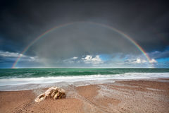 Rainbow over stone beach in Atlantic ocean Stock Photos