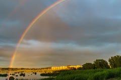 Rainbow over stony seacoast by sunset Royalty Free Stock Photos