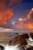 Rainbow over stormy sea. At sunset Stock Photography