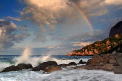 Rainbow over stormy sea. In the early morning Royalty Free Stock Photo