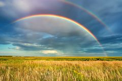 Rainbow over stormy sky in countryside at summer day stock photo