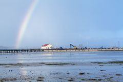 Rainbow over tidal mud flats at the coast Royalty Free Stock Photo