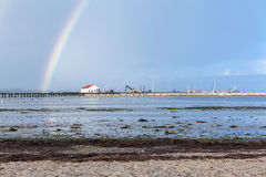 Rainbow over tidal mud flats at the coast Stock Image