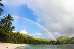 Rainbow over tropical island and white beach at Royalty Free Stock Photo